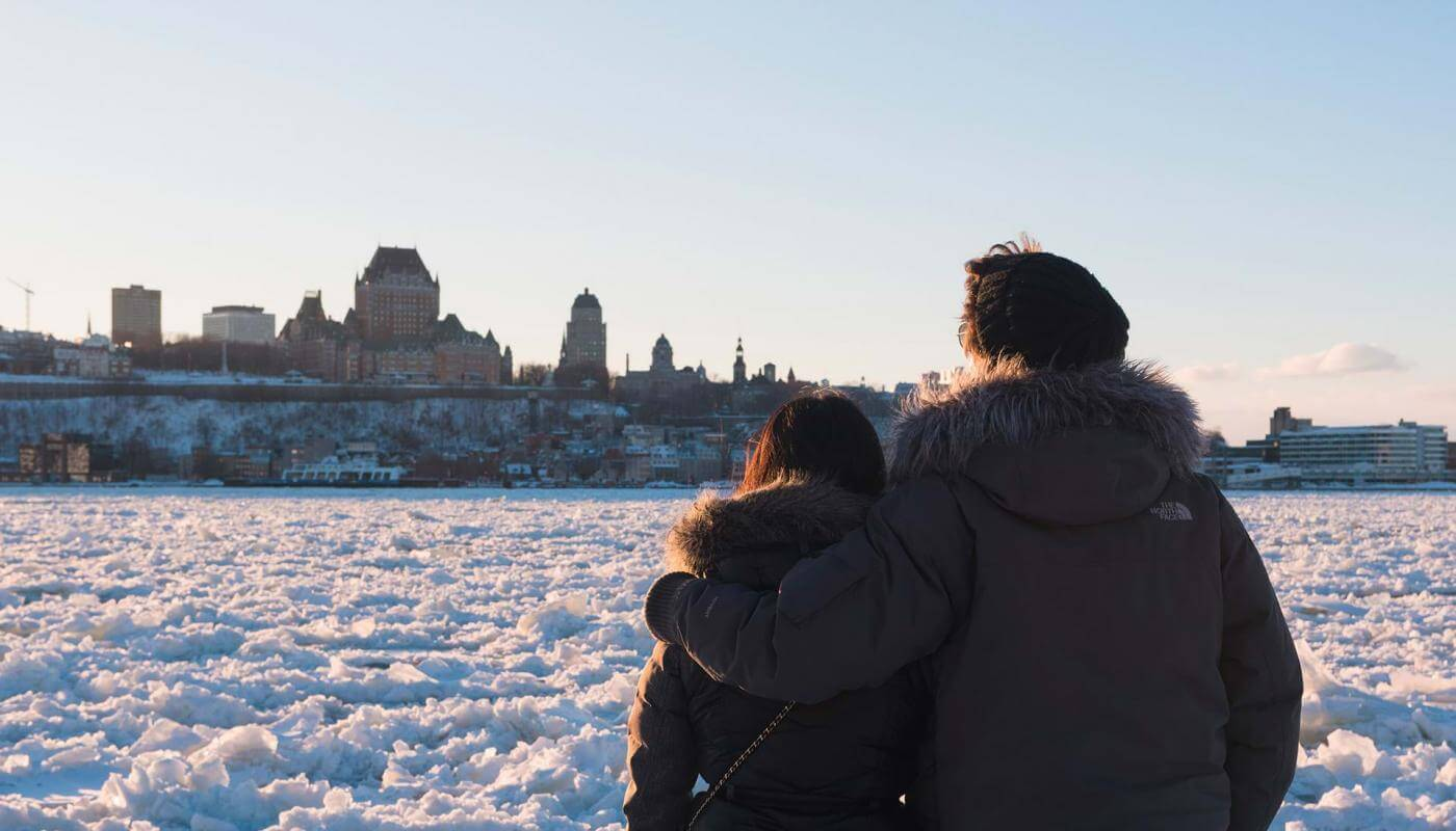 A couple watch the frozen St. Lawrence River and the panorama of Old Québec from Lévis.