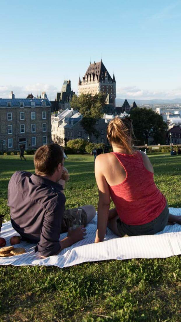 Couple picnicking near the Pierre-Dugua-De Mons terrace while admiring the Château Frontenac and the St. Lawrence River.