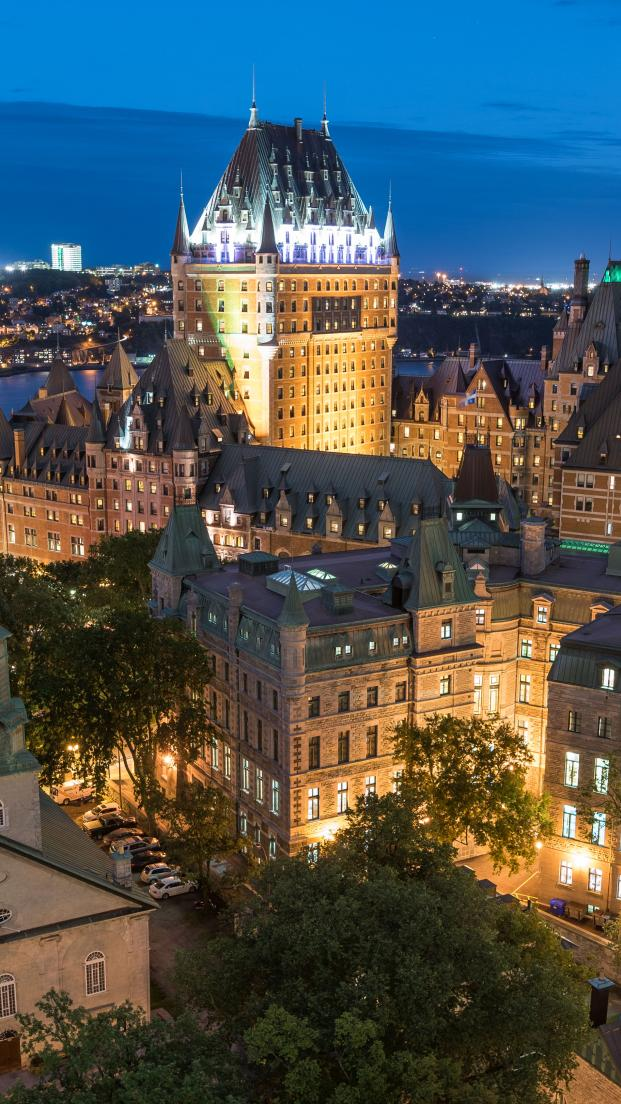Aerial view of Old Québec illuminated in the early evening, view of Chateau Frontenac and Holy Trinity Church.