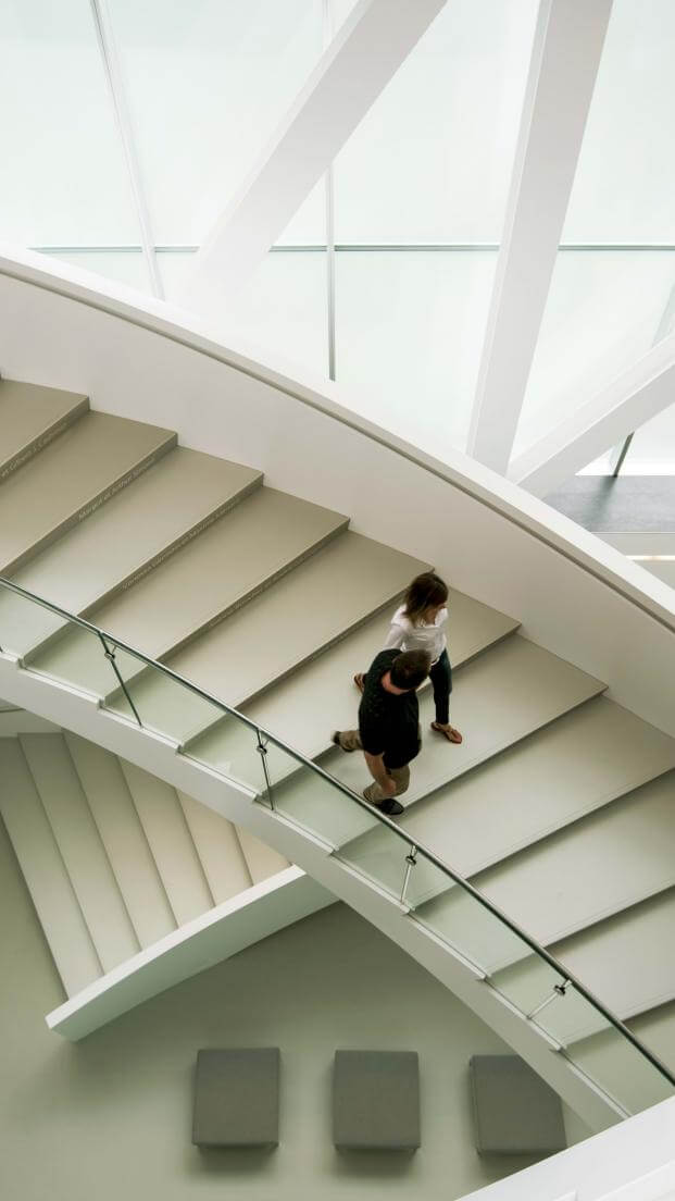 A couple descends the interior staircase of the Pierre Lassonde pavilion at the Musée national des beaux-arts du Québec.