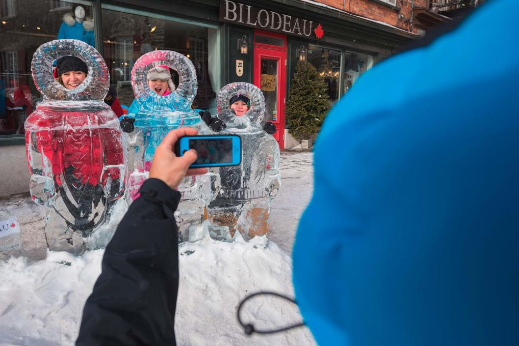 A family takes pictures with the ice sculptures in the Petit-Champlain district, during the Québec Winter Carnival.