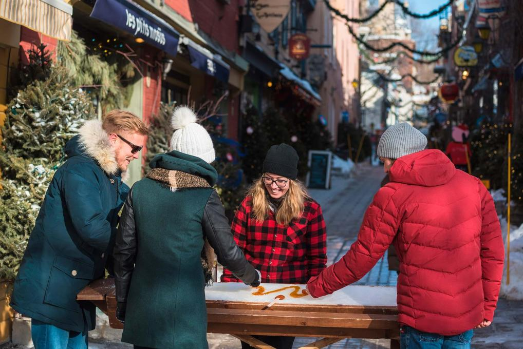 Three passers-by stop to taste maple taffy in the Petit-Champlain district.
