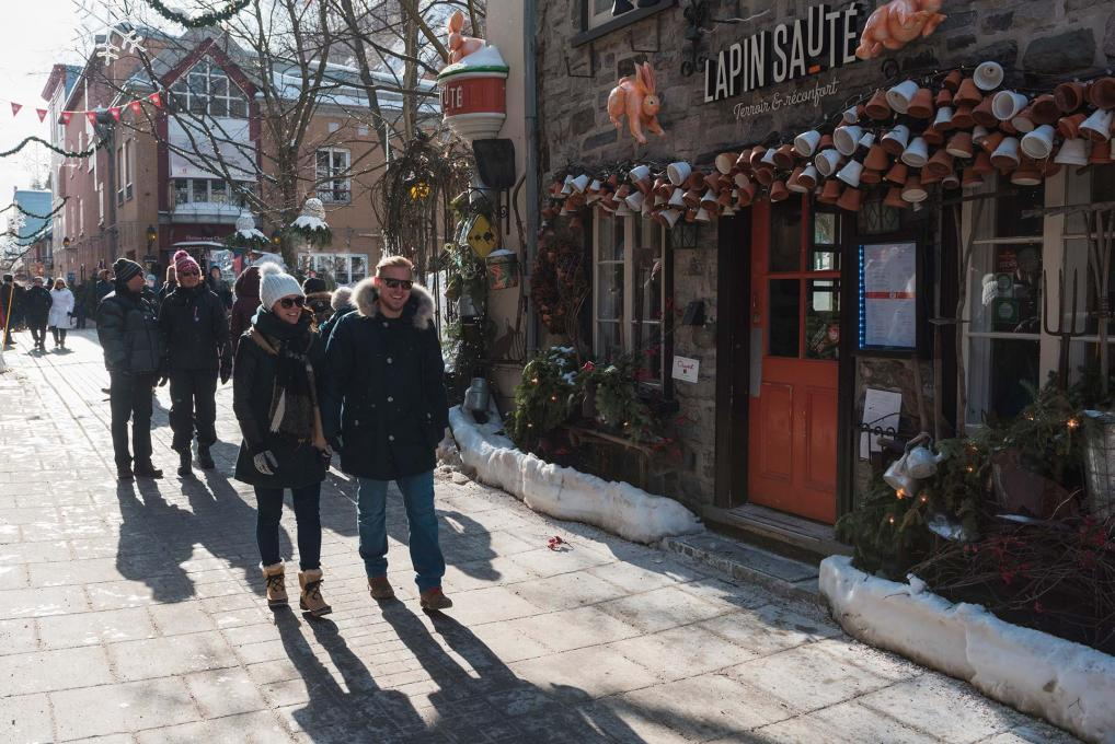 Several people walk in the rue du Petit-Champlain, near the restaurant Lapin Sauté, in Old Québec.