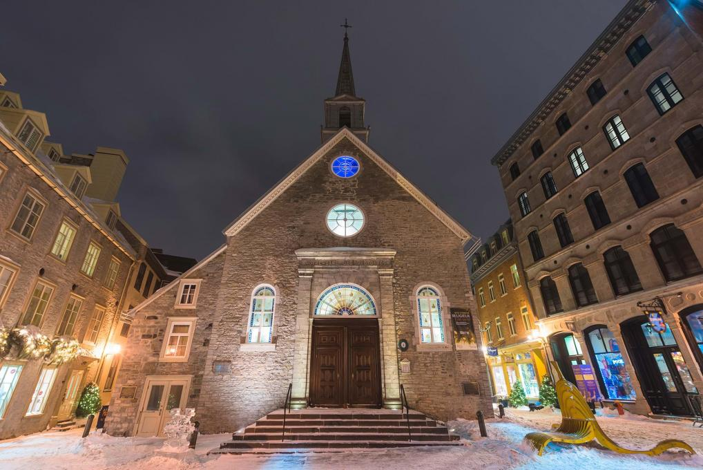 The Notre-Dame-des-Victoires church, illuminated in the evening, at Place-Royale, in the Petit-Champlain district, in winter.