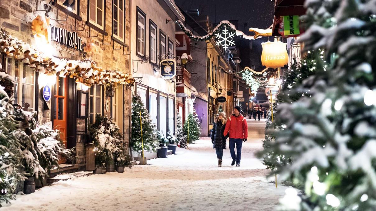 A couple takes a walk in the evening during the holiday season on rue du Petit-Champlain, covered with snow and decorated with illuminated trees.