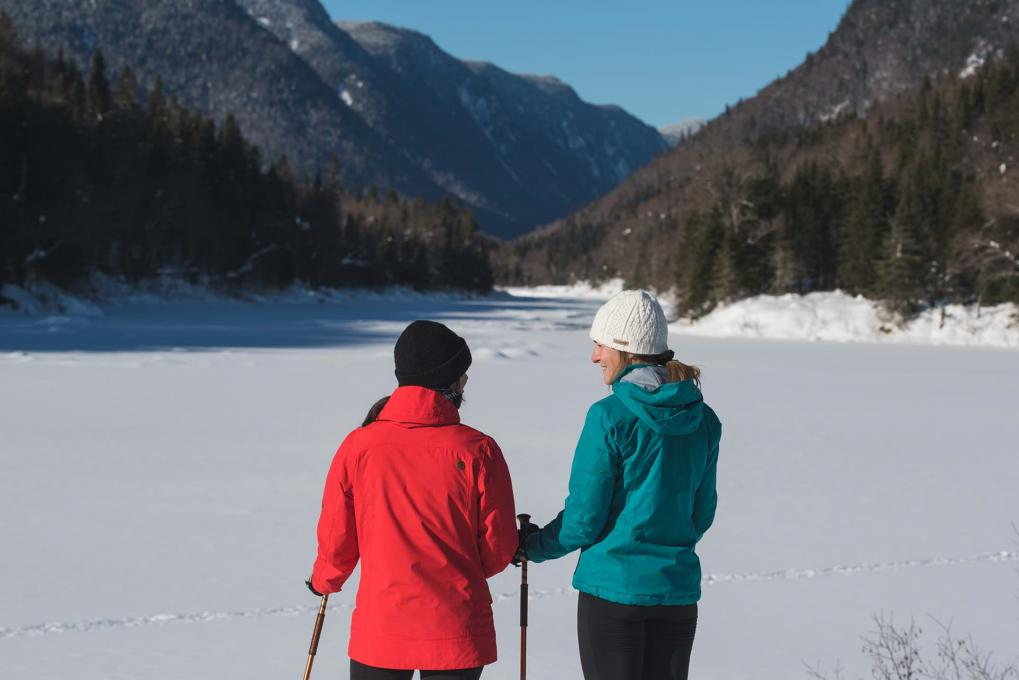 Two girls take a break in front of the snowy landscape of Jacques Cartier National Park.
