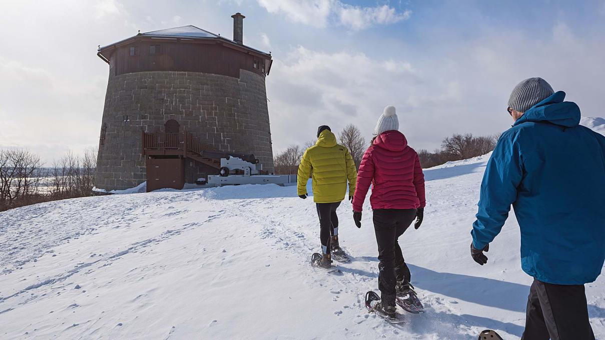 Three friends are snowshoeing on the snow-capped Plains of Abraham and heading towards the historic Martello Tower.