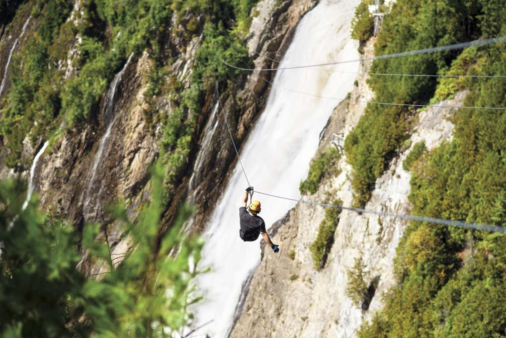 A man crosses the cove of the fall on a zip line at Parc de la Chute Montmorency.