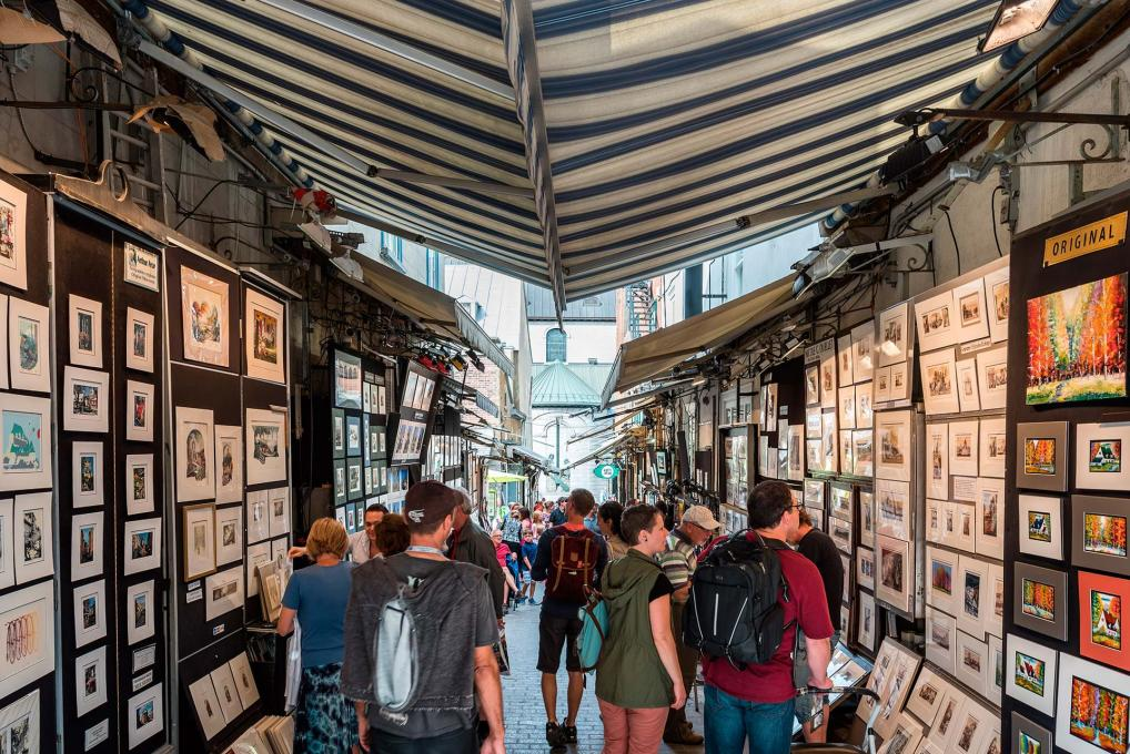 Visitors and artists chat on rue du Trésor, where several artists exhibit their works.