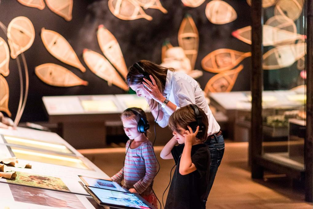 A mother and two children participate in an interactive exhibition at the Musée de la civilisation.