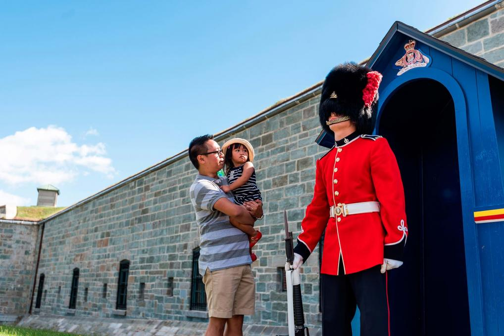 A father and his daughter watch a guard dressed in traditional uniforms in front of the front door of the Citadelle of Québec.