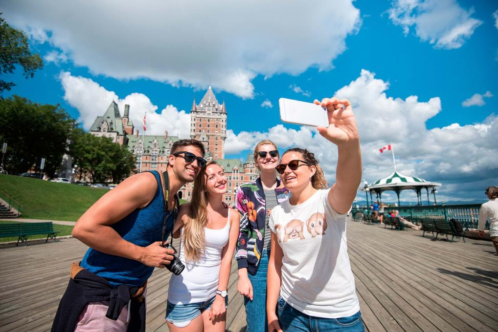 Four young adults take their picture on the Dufferin terrace, near the Château Frontenac.