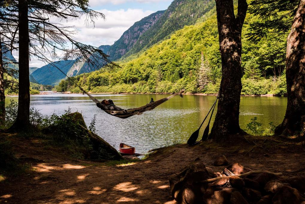 A man takes a nap in a hammock hanging from the trees on the riverside in Jacques-Cartier National Park.