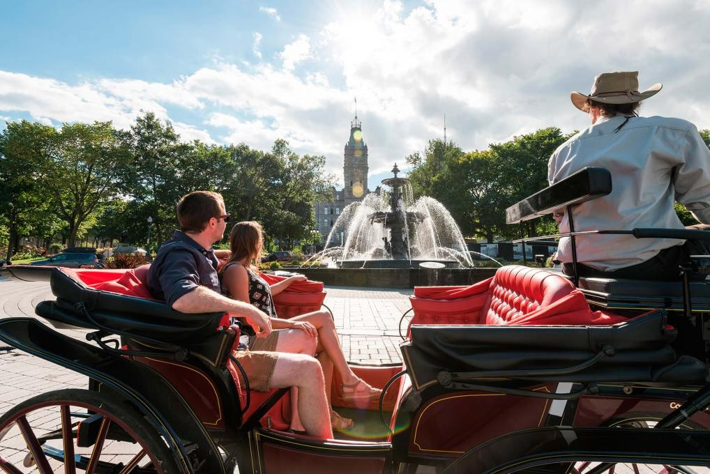 A couple enjoy a guided carriage tour in front of the Tourny fountain and the Parliament Building.