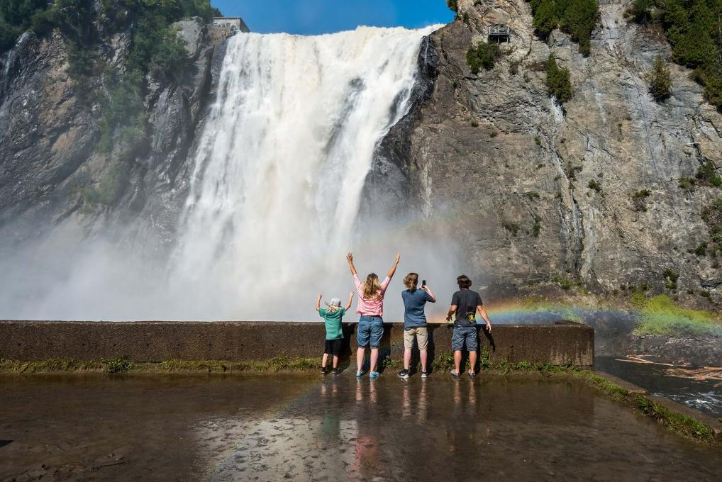 A family gets watered at the foot of the waterfall, in Chute-Montmorency Park, in summer.