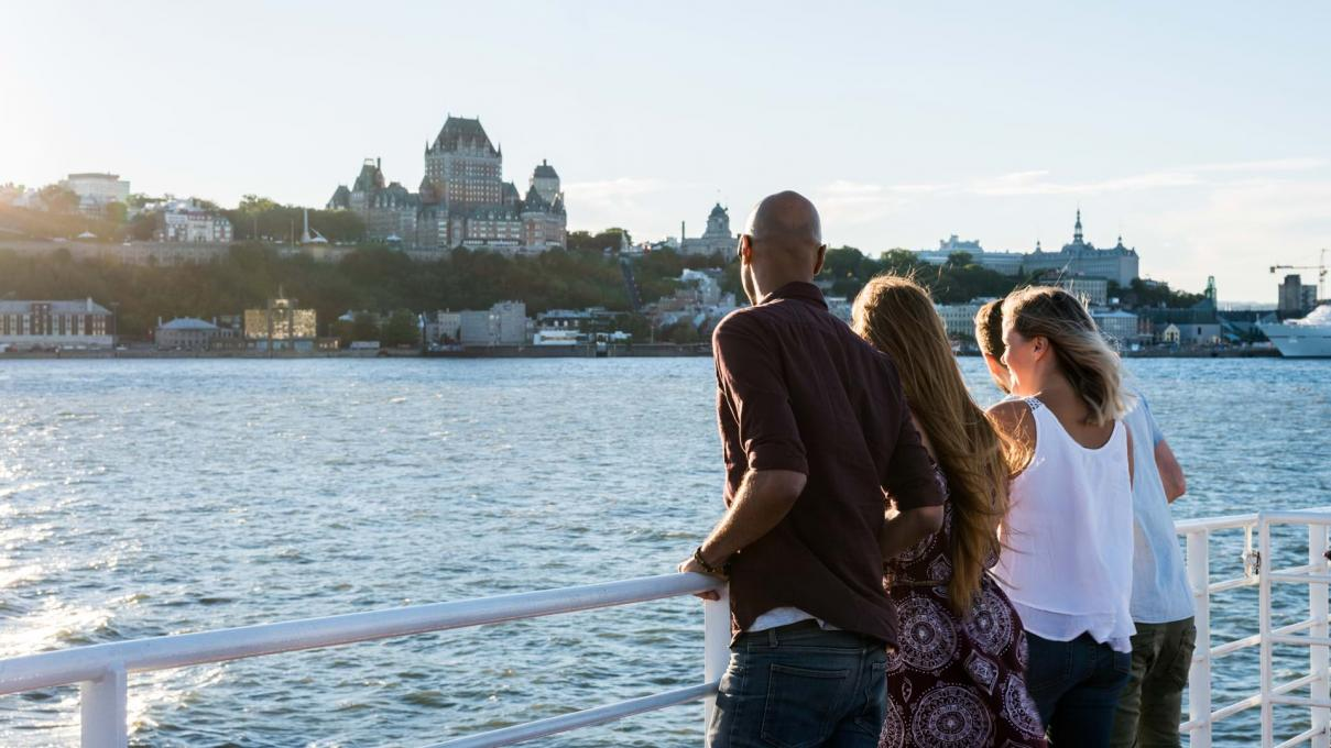 Group of friends aboard the Québec-Lévis ferry, admiring Old Québec in summer.