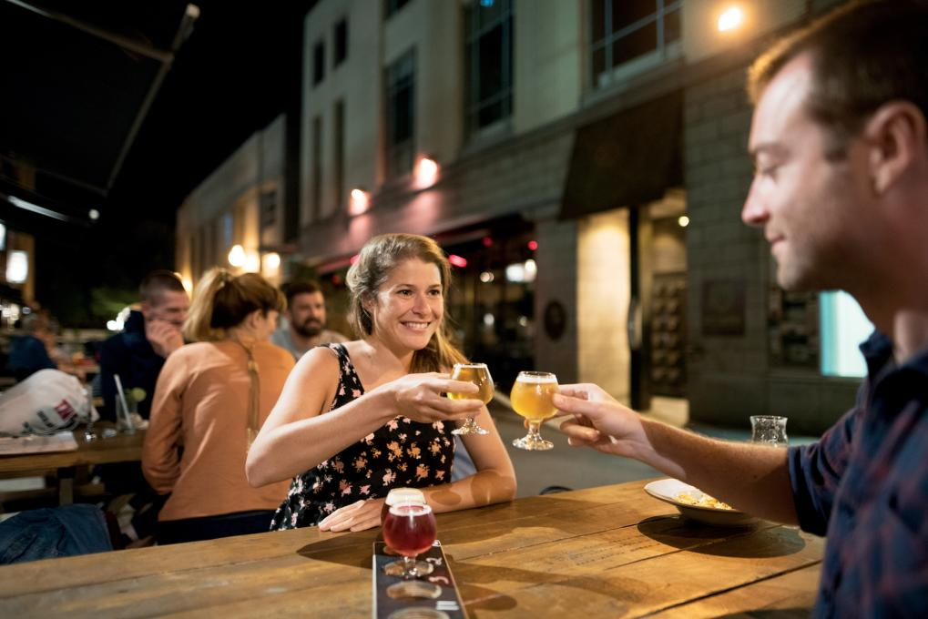 A couple enjoy microbrewery beers on a terrace in the evening.