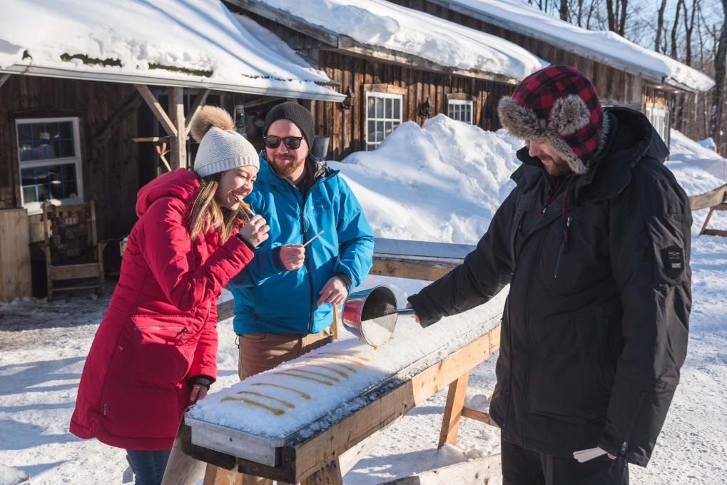 Maple taffy served to a couple at the sugar shack