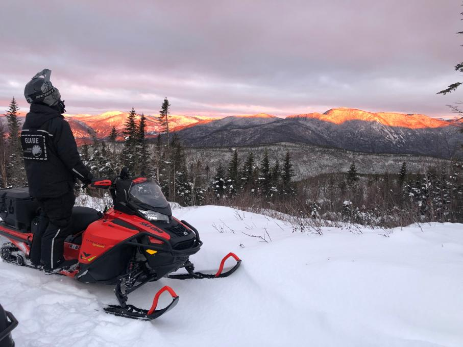 Snowmobiler looking at the sunset in the Charlevoix mountains