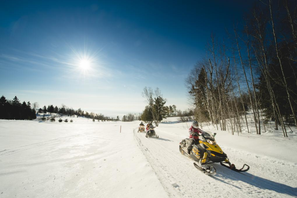 Snowmobilers riding across a snowy field in Charlevoix