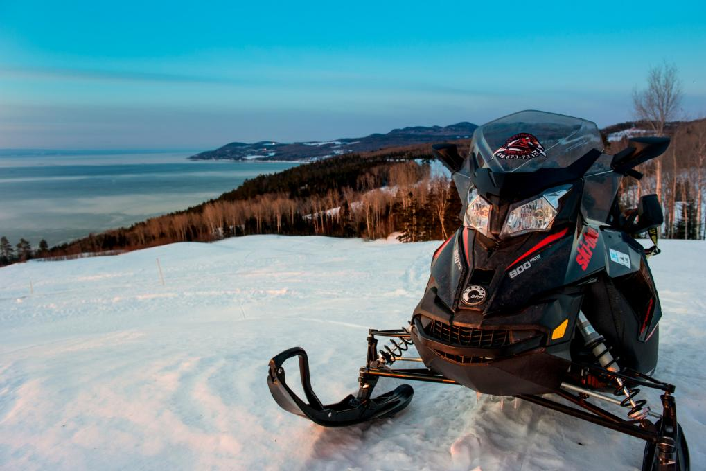 Snowmobile at the top of a mountain with a snowy background in Charlevoix