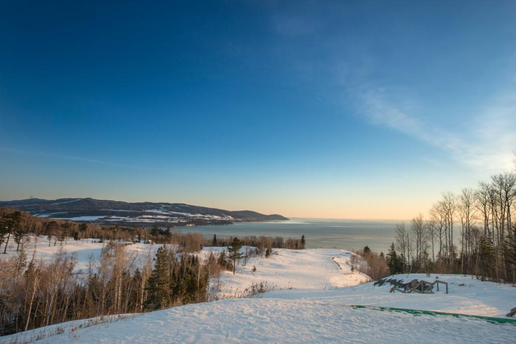 View of a snowy landscape and of the St. Lawrence River in Charlevoix