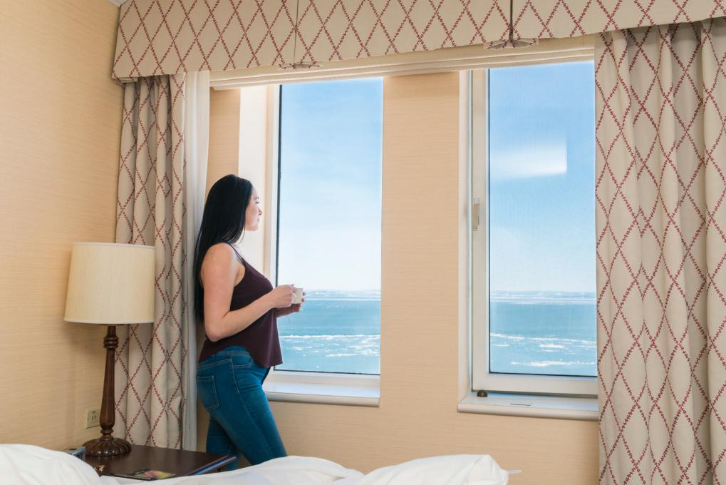 A woman is looking out a window from her hotel room