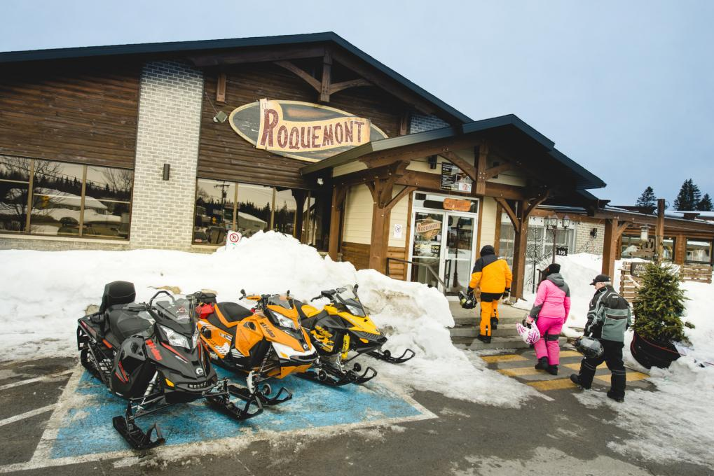 Snowmobiles parked in front of Le Roquemont