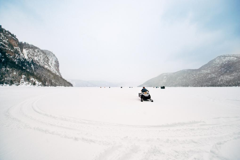 Snowmobilers passing through an ice fishing village in Saguenay-Lac-Saint-Jean,