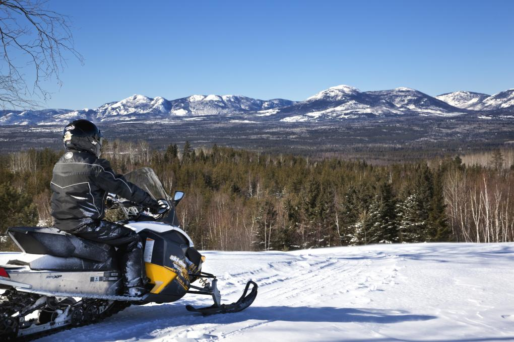Snowmobiler overlooking the snowy landscape in Charlevoix