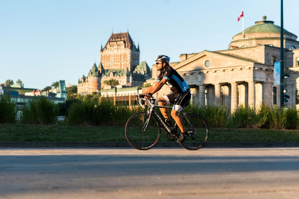 A cyclist rides on a bike path in the Old Port of Québec with the Château Frontenac in the background.