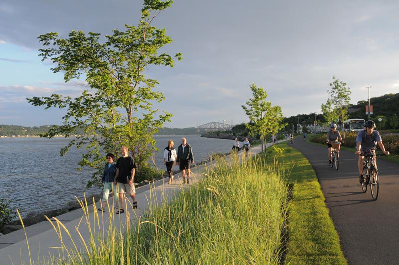Walkers and cyclists on the Promenade Samuel-De Champlain along the St. Lawrence River