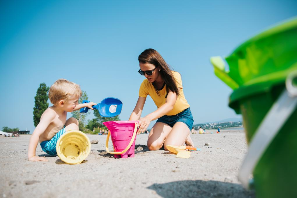 A mother and her child play to build a sand castle at the beach of Baie de Beauport.