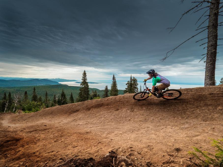 A cyclist enjoys the trails and the beautiful view on a mountain bike in the Massif de Charlevoix.