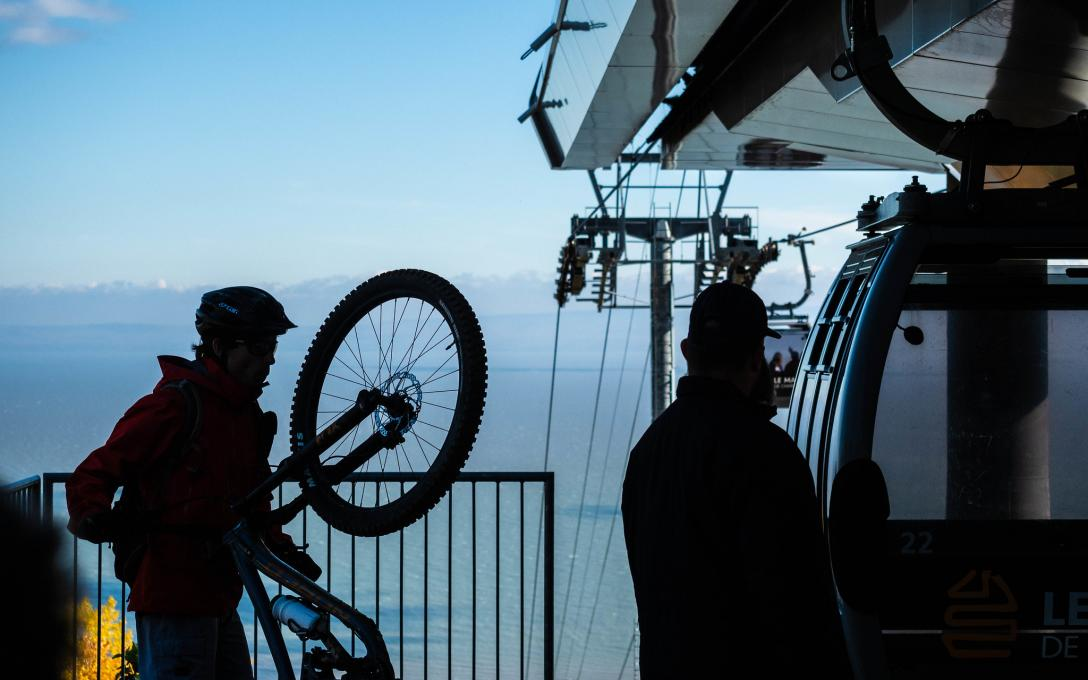 A cyclist boards a cable car with his bike in the Massif de Charlevoix.