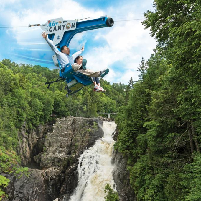 Deux personnes traversent le canyon Sainte-Anne, assises dans le AirCanyon duo.