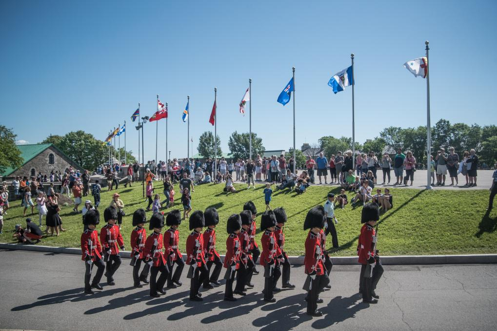 A crowd watches the changing of the guard with soldiers in red uniforms at La Citadelle in Québec in summer.