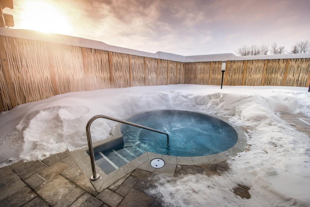 View of an outdoor thermal bath in winter at the Aroma Spa at Village Vacances Valcartier.