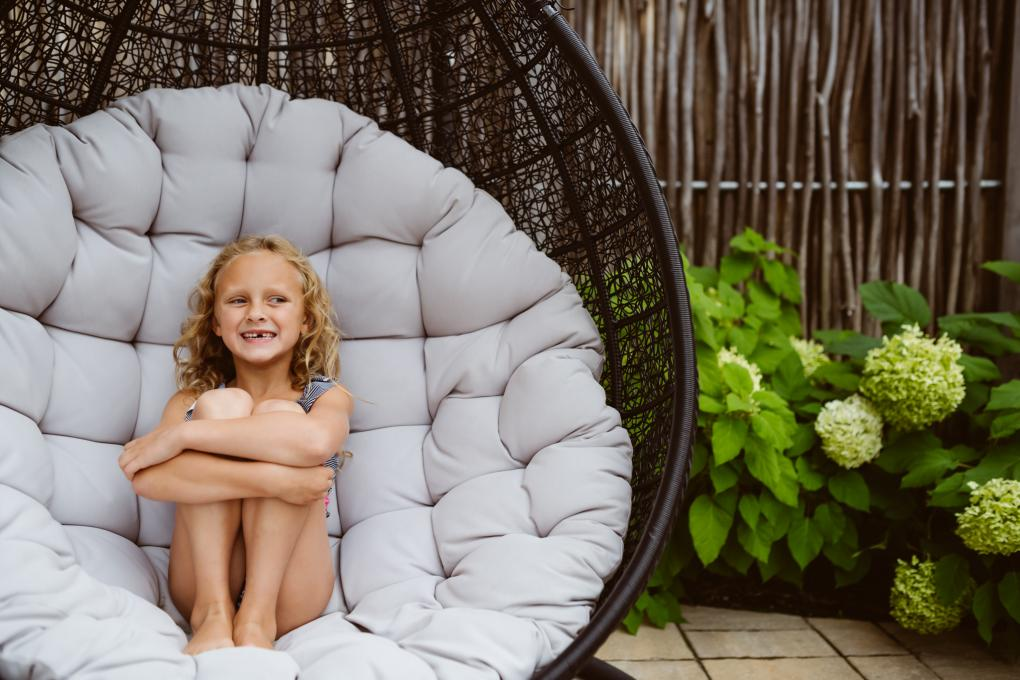 A little girl sits in an outdoor chair on the terrace of the Aroma Spa at Village Vacances Valcartier.