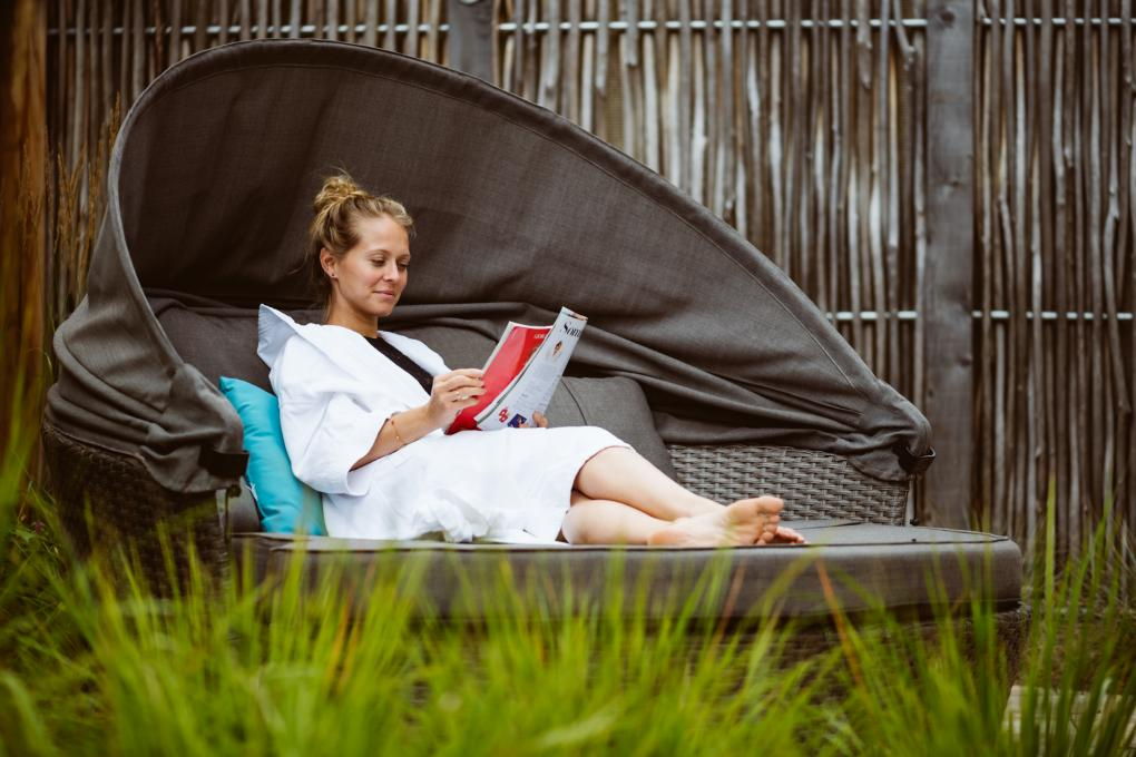 A woman reads a magazine on the outdoor terrace of the Aroma Spa at Village Vacances Valcartier.