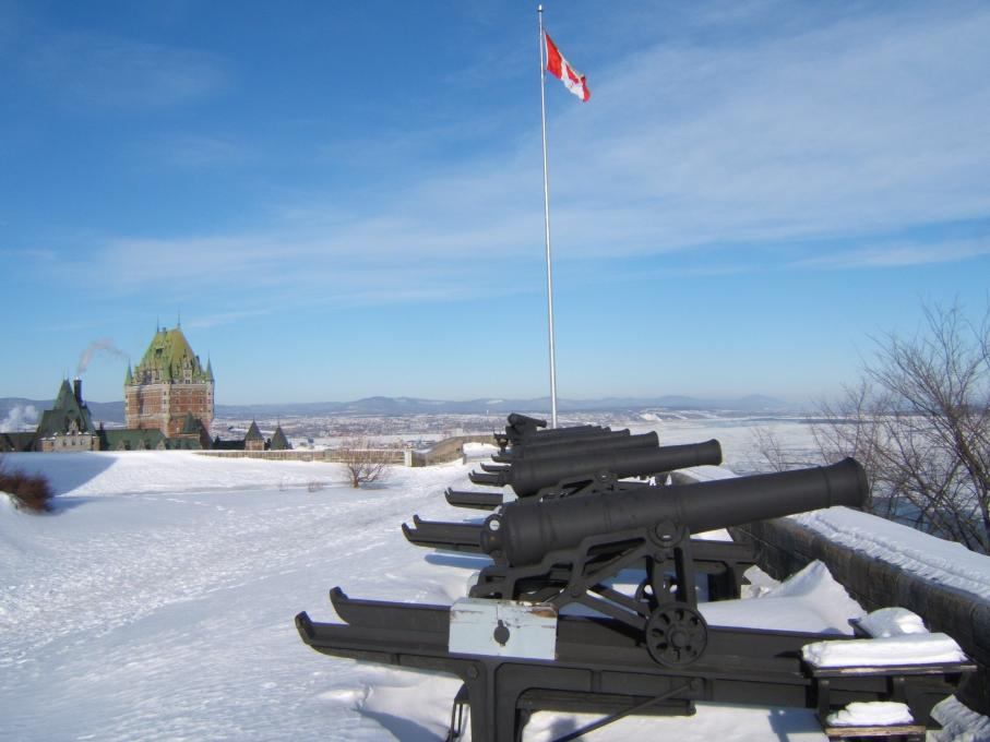Several cannons in winter, in the snowy exterior courtyard of La Citadelle de Québec, with a view of the Château Frontenac.