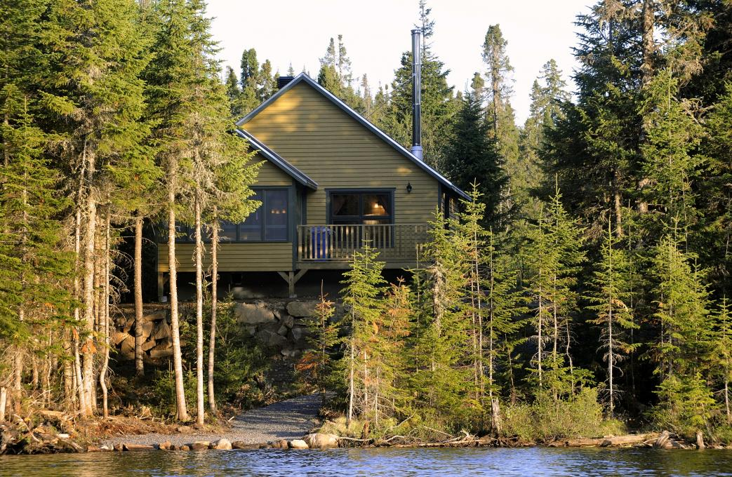 Exterior view of a chalet in the forest, on the edge of a lake, in the Réserve faunique des Laurentides, in summer.