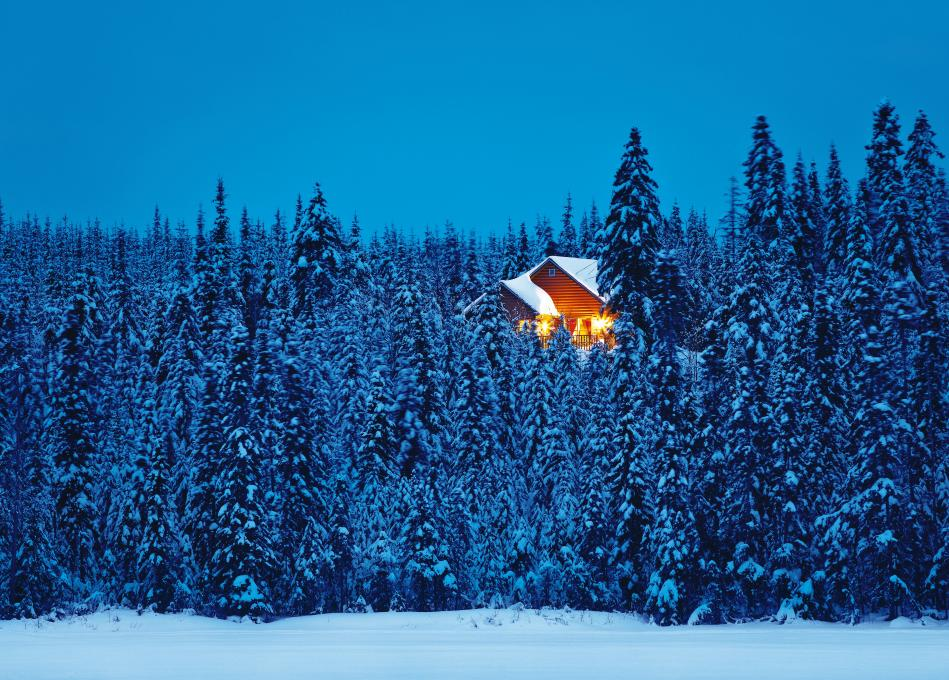 Exterior view of an illuminated chalet in the heart of a snowy forest, in the Réserve faunique des Laurentides, in winter.