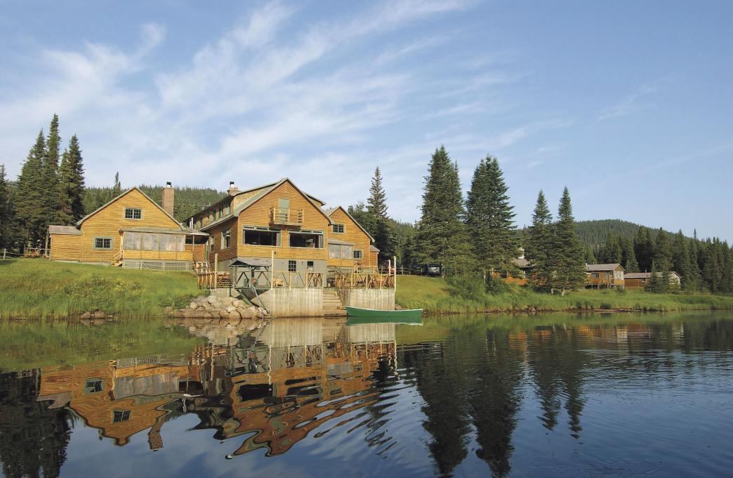 Exterior view of several chalets on the edge of a lake, in the Réserve faunique des Laurentides, in summer.