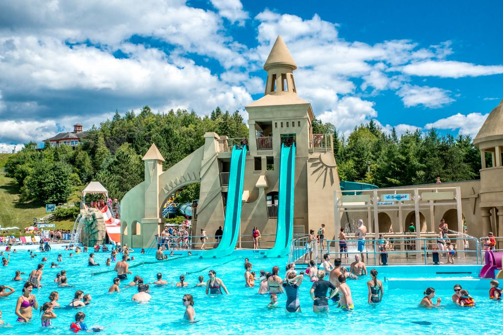 Water slides and outdoor swimming pool at Village Vacances Valcartier, in summer.