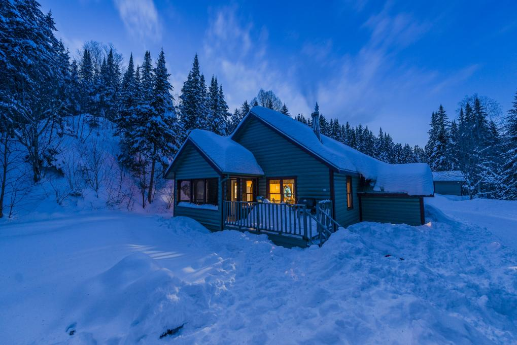 Exterior view of a chalet in winter, in the snowy forest of the Portneuf Wildlife Reserve.