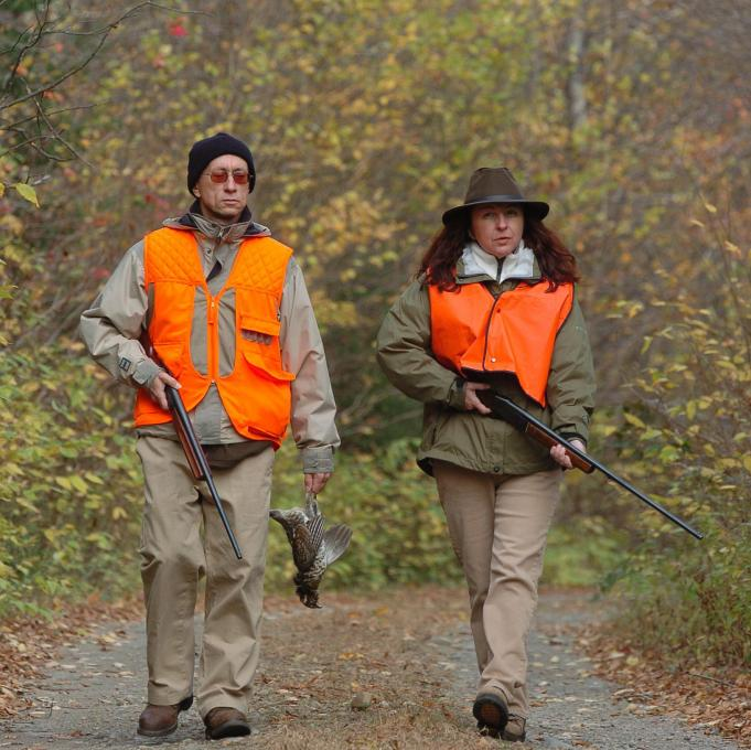 Two hunters, rifles in hand, on a trail in autumn, in the Portneuf Wildlife Reserve.