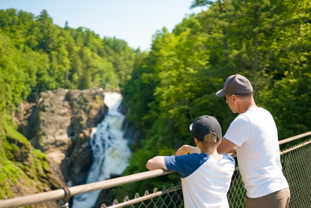 A man and his child observe the fall from the McNicoll Bridge in Sainte-Anne Canyon.