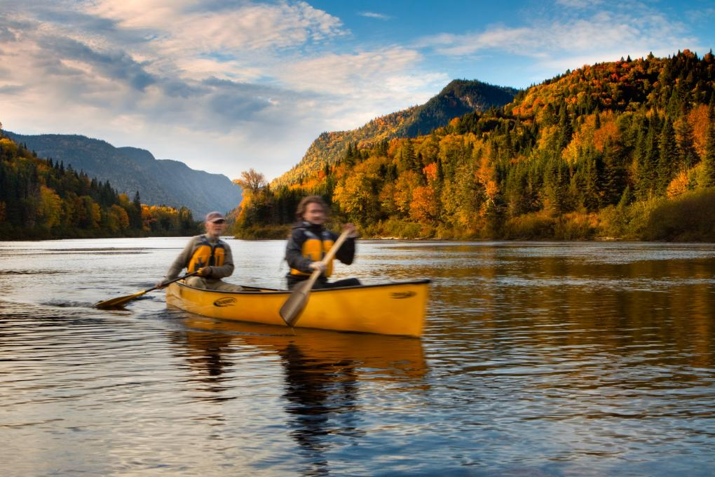 Two people in a canoe in the fall in the Jacques-Cartier Valley, in the Jacques-Cartier National Park.