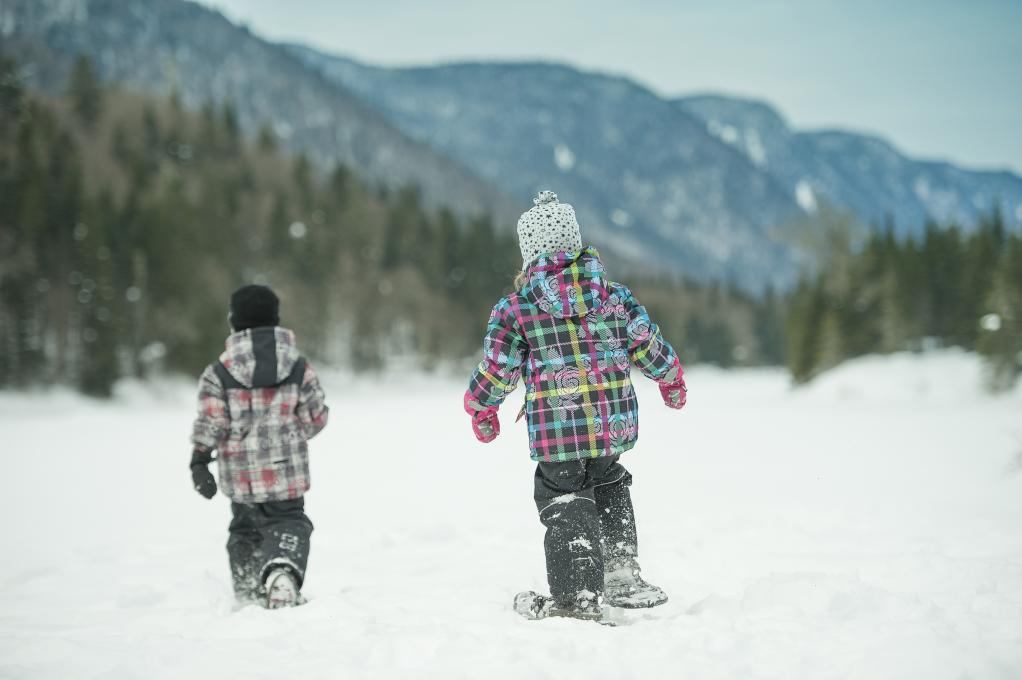 Two children on snowshoes in the Jacques-Cartier National Park, in winter.